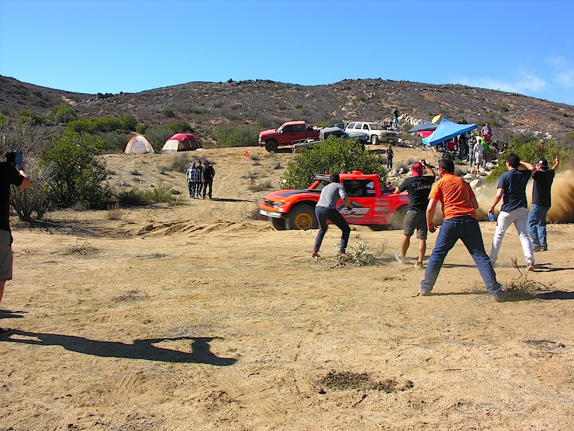 Spectators cheering on a trophy truck at the Baja 1000